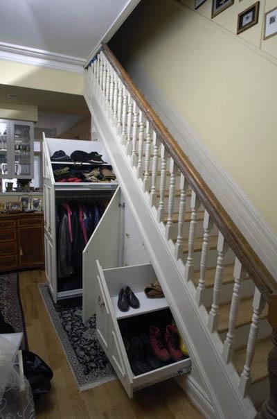 Скосное пространство под лестницей оформлено не встроенным шкафом купе.