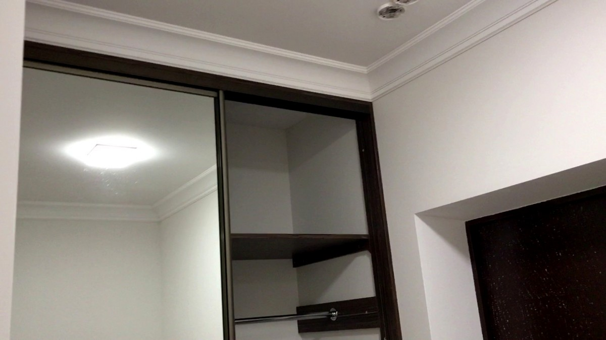 Пример эстетичного способа сопряжения шкафа купе, натяжного потолка и потолочного плинтуса